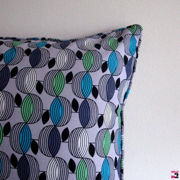 Coussin rectangulaire gris avec un motif en bleu vert