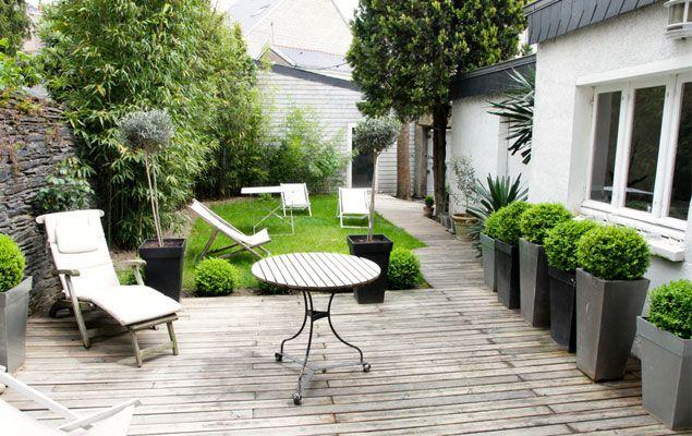 Pots dans un petit jardin avec terrasse en bois et