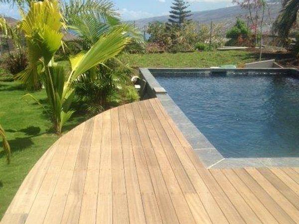 Piscine avec terrasse en bois et revêtement carrelage