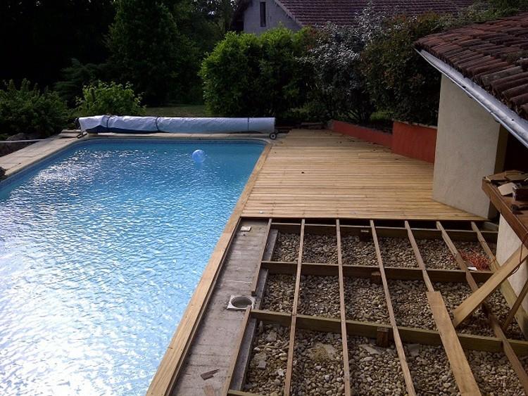 Une terrasse en bois autour de la piscine